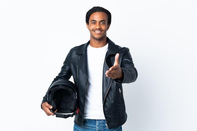 Uomo afroamericano con le trecce che tiene un casco del motociclo su bianco che agitano le mani per chiudere un buon affare