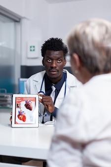 Uomo afroamericano con occupazione medico utilizzando tablet