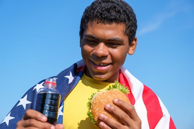 Uomo afroamericano con bandiera che si gode hamburger e bevanda cola all'aperto