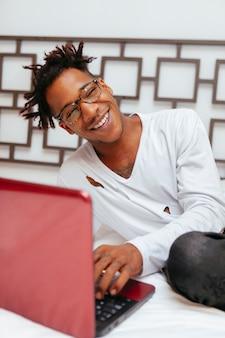 Uomo afroamericano che lavora alla camera da letto del computer. giovane peccato maschio sul letto bianco al collegamento ad internet.