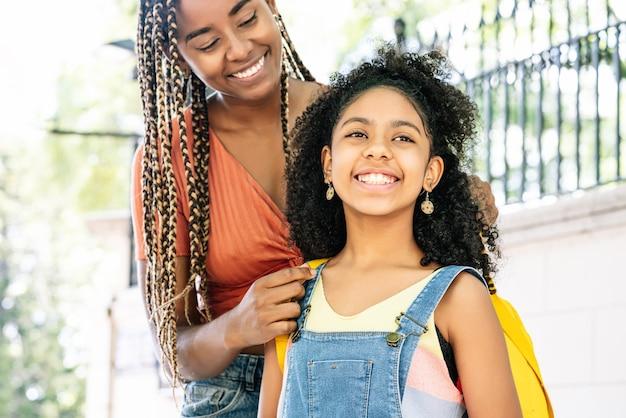 Madre afroamericana che porta sua figlia a scuola. concetto di educazione.