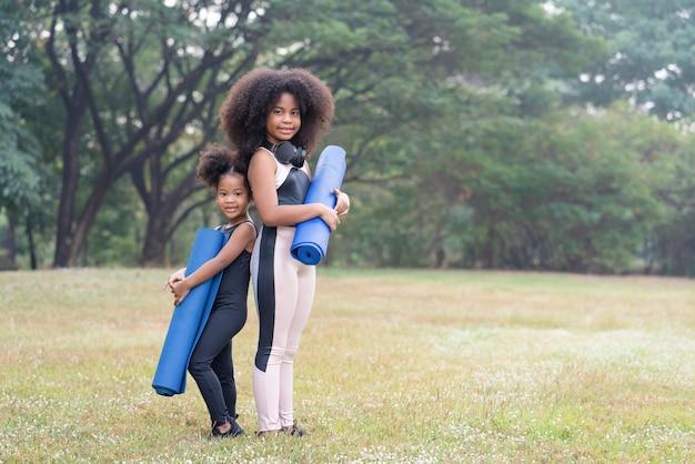 La sorella maggiore afroamericana e la sorella minore in piedi tengono il tappetino per la pratica dello yoga nel parco all'aperto