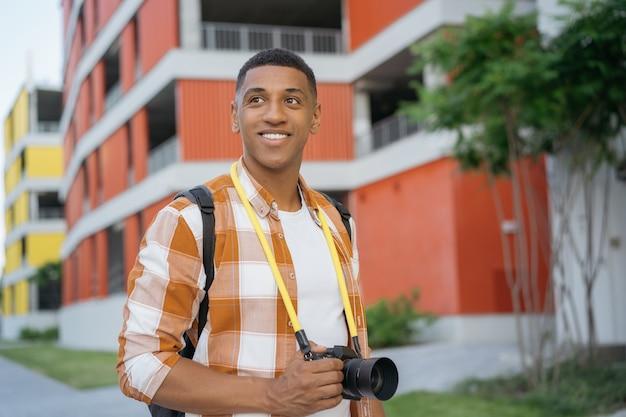 Fotografo afroamericano che cammina per strada turista sorridente che tiene in mano una fotocamera digitale