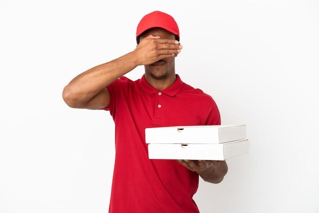 Uomo afroamericano di consegna della pizza che prende le scatole della pizza sopra gli occhi bianchi isolati della copertura della parete a mano. non voglio vedere qualcosa