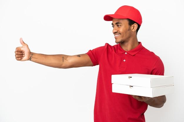 Uomo afroamericano di consegna della pizza che prende le scatole della pizza sopra la parete bianca isolata che dà un gesto del pollice