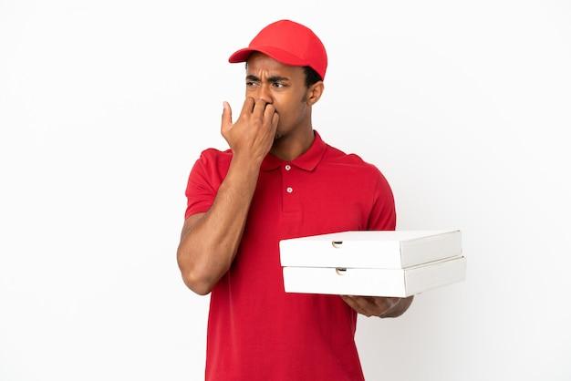 Uomo afroamericano di consegna della pizza che prende le scatole della pizza sopra la parete bianca isolata avendo dubbi