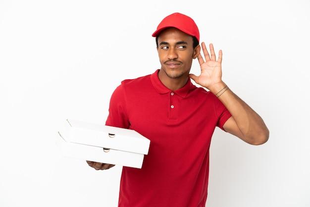 Uomo afroamericano di consegna della pizza che prende le scatole della pizza sopra il muro bianco isolato ascoltando qualcosa mettendo la mano sull'orecchio