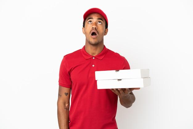 Fattorino afroamericano della pizza che prende le scatole della pizza sopra la parete bianca isolata che guarda in su e con espressione sorpresa
