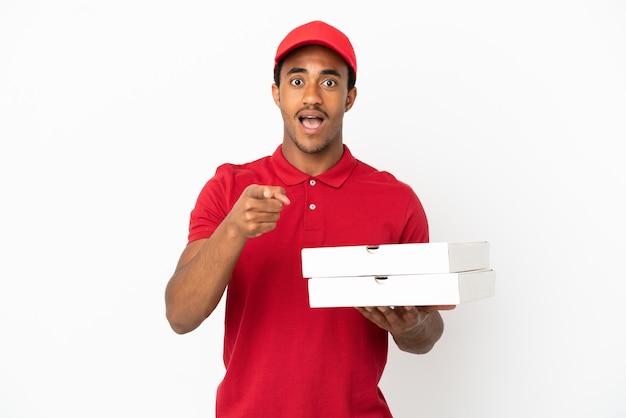 Il fattorino afroamericano della pizza che prende le scatole della pizza sopra la parete bianca isolata ha sorpreso e che indica front