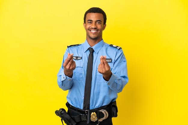 Uomo di polizia afroamericano sopra fondo giallo isolato che fa il gesto dei soldi