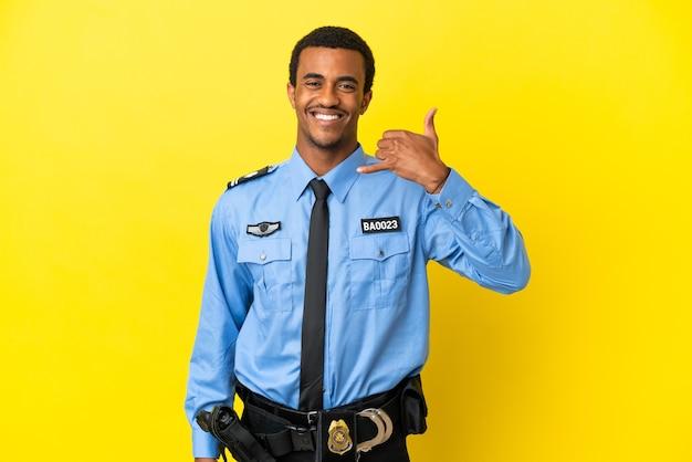 Poliziotto afroamericano sopra il muro giallo isolato che fa il gesto del telefono