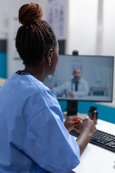Assistente praticante afroamericano che discute i sintomi del virus