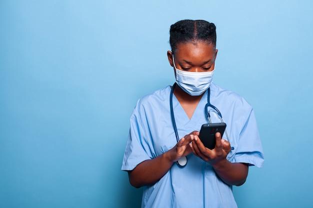 Infermiera praticante afroamericana con maschera protettiva contro il coronavirus