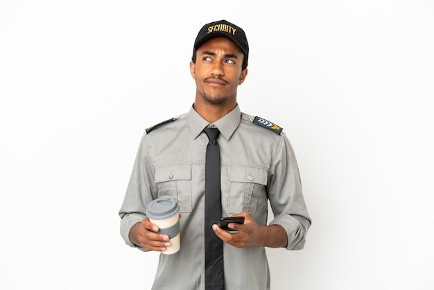 Salvaguardia afroamericana su sfondo bianco isolato che tiene caffè da portare via e un cellulare mentre pensa a qualcosa