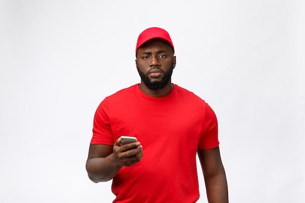 Telefonata seria dell'uomo di consegna afroamericano sul suo telefono cellulare con un'espressione seria