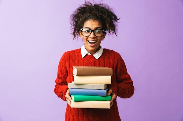 Ragazza sorridente dell'afroamericano in uniforme scolastica che tiene mazzo di libri, isolata