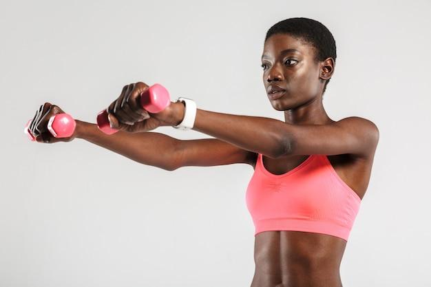 African american sportive facendo esercizio con manubri isolate su muro bianco