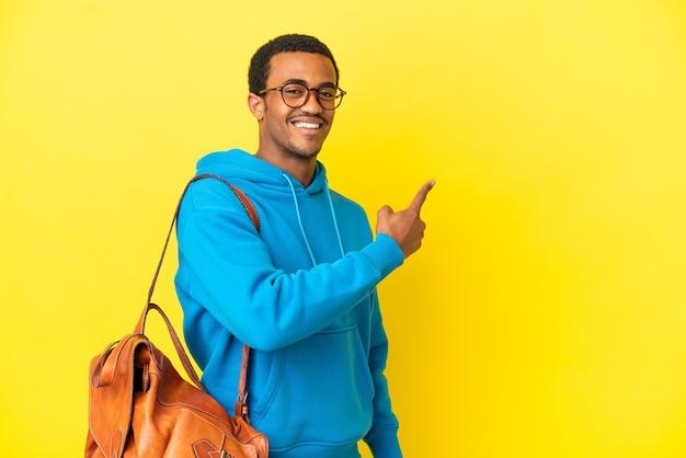 Uomo studente afroamericano su sfondo giallo isolato che punta indietro