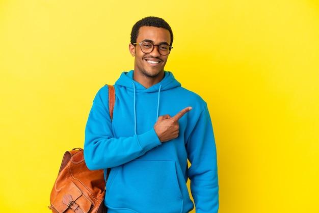 Studente afroamericano su sfondo giallo isolato che punta al lato per presentare un prodotto