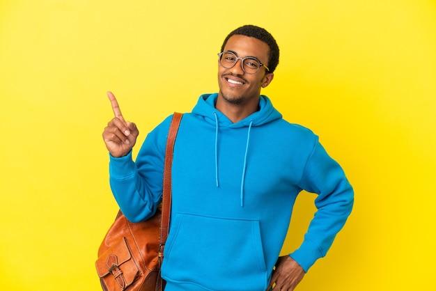 Uomo studente afroamericano su sfondo giallo isolato che mostra e solleva un dito in segno del meglio