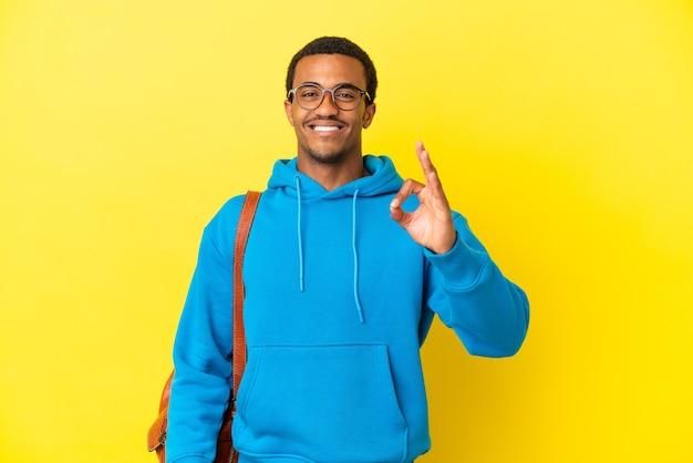 Uomo studente afroamericano su sfondo giallo isolato che mostra segno ok con le dita