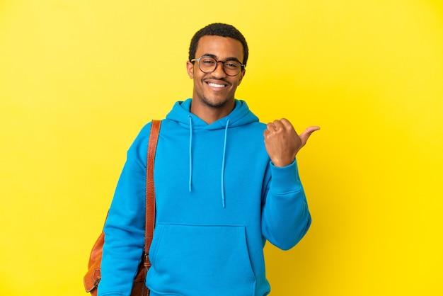 Studente afroamericano sopra la parete gialla isolata che punta al lato per presentare un prodotto