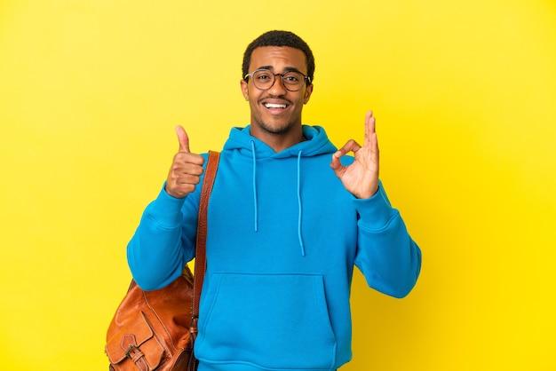 Studente afroamericano sopra il muro giallo isolato che mostra il segno ok e il gesto del pollice in alto