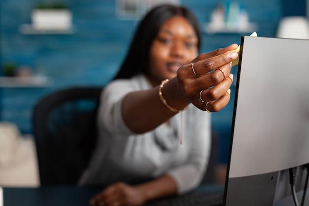 Studente afroamericano che mette note adesive sul computer che lavora a distanza da casa