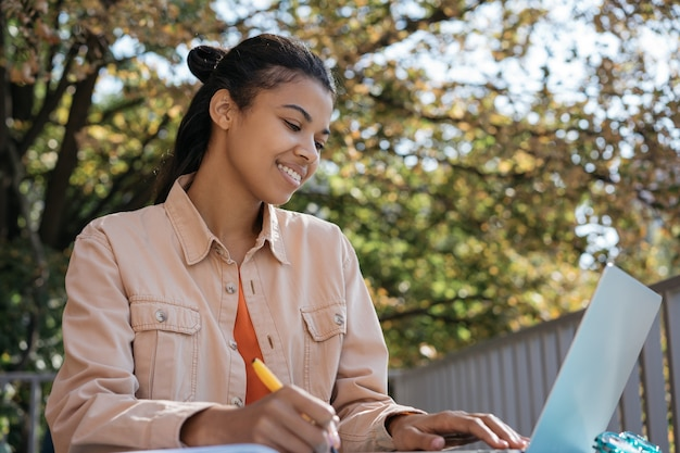 Studente afroamericano utilizzando laptop, studiando online, imparando la lingua
