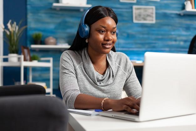 Studente afroamericano che indossa le cuffie che naviga tra le informazioni che compongono l'articolo del blog