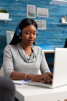 Studente afroamericano che indossa l'auricolare che naviga tra le informazioni online lavorando al webinar di comunicazione