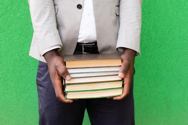 Studente afroamericano con un libro su uno sfondo verde