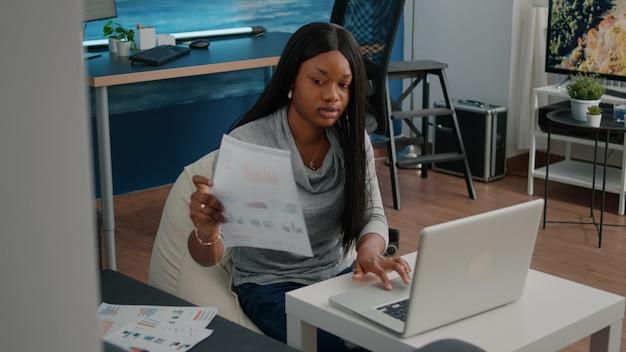 Studente afroamericano che lavora a distanza da casa alle statistiche di marketing digitando grafici finanziari