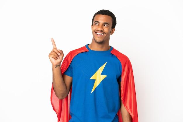 Uomo afroamericano super eroe su sfondo bianco isolato rivolto verso l'alto e sorpreso