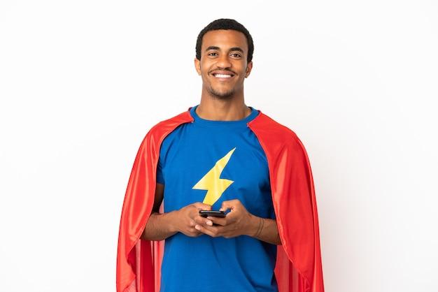 Uomo supereroe afroamericano su sfondo bianco isolato inviando un messaggio con il cellulare