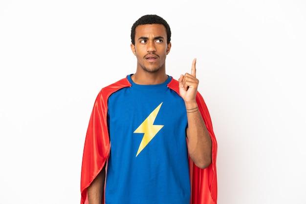 Uomo supereroe afroamericano su sfondo bianco isolato pensando a un'idea che punta il dito verso l'alto