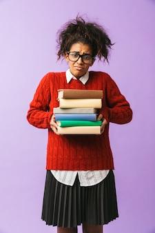 Adolescente afroamericano in uniforme scolastica che tiene mazzo di libri, isolato