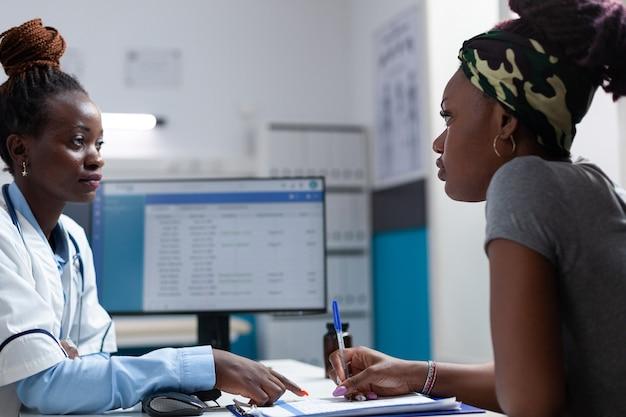 Medico terapista afroamericano che spiega il trattamento sanitario