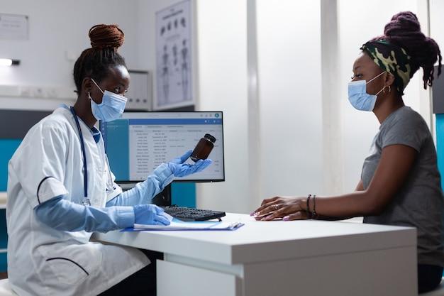 Medico terapista afroamericano che tiene in mano una bottiglia di pillole che spiega il trattamento farmacologico