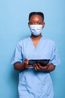 Infermiera terapista afroamericana con maschera protettiva per prevenire l'infezione da coronavirus