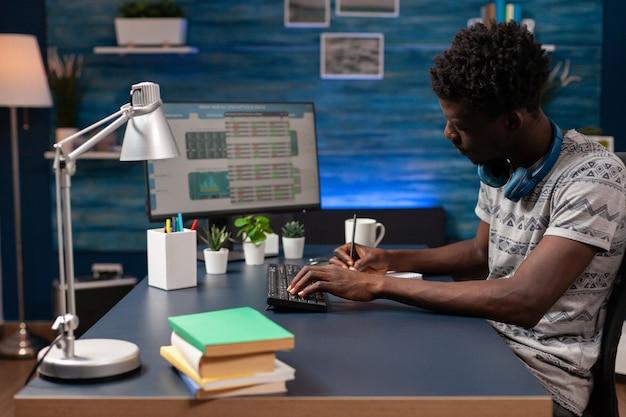 Commerciante afroamericano che analizza le informazioni sul valore del mercato azionario sul computer