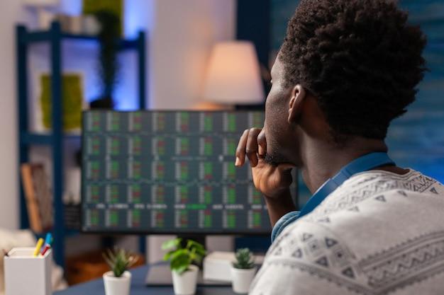 Operaio commerciante afroamericano che controlla il grafico del mercato azionario sul computer