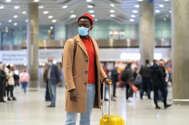 L'uomo viaggiatore afroamericano con la valigia si trova nel terminal dell'aeroporto
