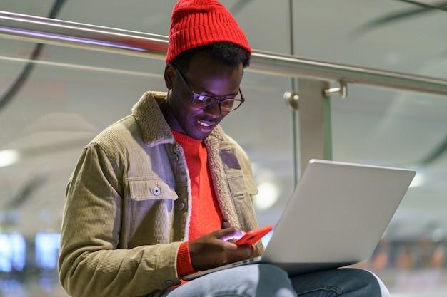 Uomo del millenario viaggiatore afroamericano che riposa e che si siede sul pavimento in aeroporto tramite cellulare