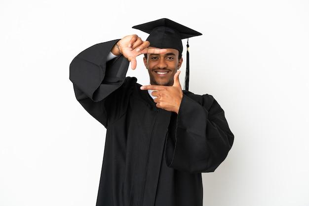Uomo laureato afroamericano sopra fondo bianco isolato che mette a fuoco il fronte. simbolo di inquadratura
