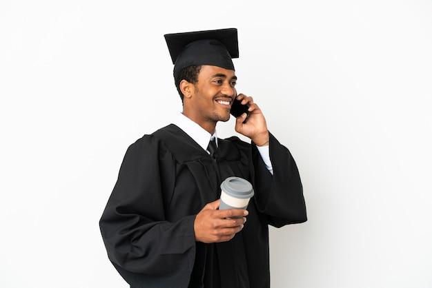 Uomo afroamericano laureato su sfondo bianco isolato tenendo il caffè da asporto e un mobile