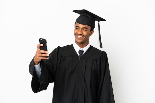 Uomo laureato afroamericano sopra fondo bianco isolato che fa un selfie