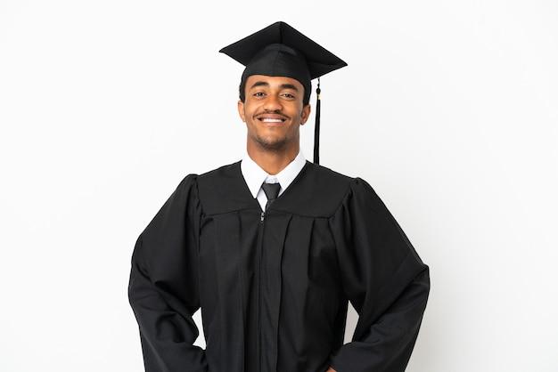 Uomo afroamericano laureato su sfondo bianco isolato in posa con le braccia all'anca e sorridente