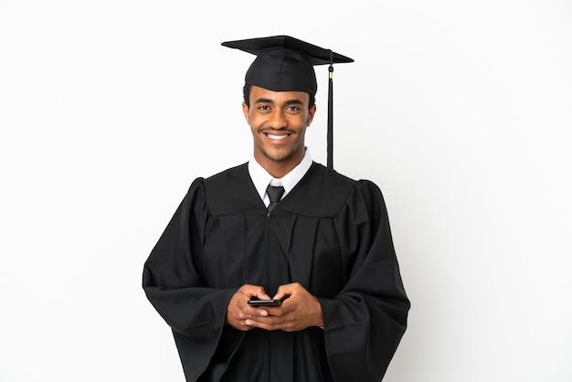 Uomo laureato afroamericano su sfondo bianco isolato inviando un messaggio con il cellulare