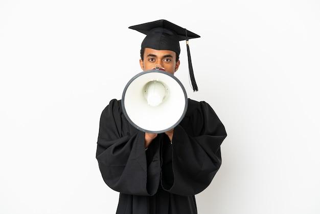 Uomo afroamericano laureato su sfondo bianco isolato che grida attraverso un megafono